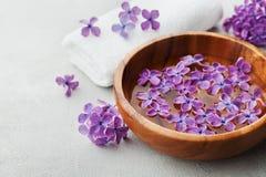 温泉和健康构成与充满香气的丁香开花水在木碗和特里毛巾在石背景,芳香疗法 免版税库存照片