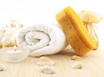 温泉和健康设置与毛巾、海绵、奶油和蜡烛 免版税库存照片