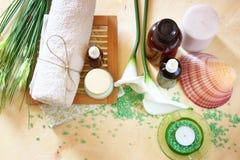 温泉和健康设置与自然肥皂、蜡烛和毛巾。自然木背景。绿色集合。 免版税库存图片