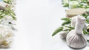 温泉和秀丽治疗背景与按摩草本球、花、工具和辅助部件在白色,框架 图库摄影