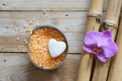 温泉在木桌上设置了、椰子和兰花腌制槽用食盐、花和白色石头以心脏的形式,自然竹子 库存图片