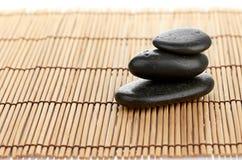 温泉在竹背景的一块石头 免版税库存照片
