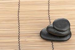 温泉在竹背景的一块石头 免版税库存图片