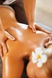 温泉妇女后面按摩 浴秀丽构成油用肥皂擦洗处理 身体,护肤疗法 库存照片