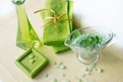 温泉成套工具:液体皂,海盐,绿色毛巾,鲜花,橄榄在白色背景的一块老黄色餐巾离开 图库摄影