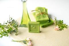 温泉成套工具:液体皂,海盐,绿色毛巾,鲜花,橄榄在白色背景的一块老黄色餐巾离开 免版税库存照片