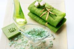 温泉成套工具:液体皂,海盐,绿色毛巾,鲜花,橄榄在白色背景的一块老黄色餐巾离开 库存图片