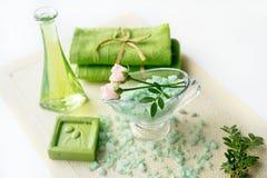 温泉成套工具:液体皂,海盐,绿色毛巾,鲜花,橄榄在白色背景的一块老黄色餐巾离开 免版税图库摄影