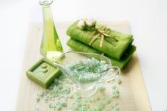 温泉成套工具:液体皂,海盐,绿色毛巾,鲜花,橄榄在白色背景的一块老黄色餐巾离开 库存照片