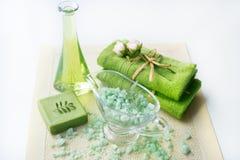 温泉成套工具:液体皂,海盐,绿色毛巾,鲜花,橄榄在白色背景的一块老黄色餐巾离开 免版税库存图片