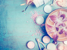 温泉或健康设置与化妆产品、水碗和兰花在蓝色绿松石破旧的别致的背景,顶视图开花 库存图片
