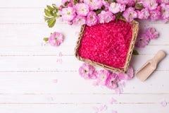 温泉或健康设置 在碗的桃红色海盐和桃红色花 免版税库存照片