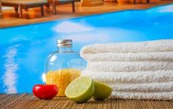 温泉按摩与毛巾被堆积的,红色蜡烛和石灰的边界背景在游泳池附近 免版税图库摄影
