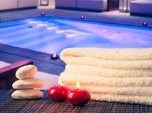温泉按摩与毛巾被堆积的,红色蜡烛和石近的游泳池的边界背景 图库摄影