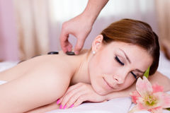 温泉放松:获得美丽的年轻白肤金发的夫人享受放松的乐趣在石疗法按摩&芳香疗法期间 免版税库存图片