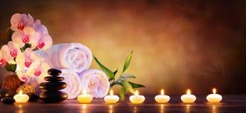 温泉概念-与毛巾和蜡烛的按摩石头 免版税库存图片