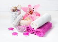 温泉概念 桃红色百合花,海盐,蜡烛,毛巾 免版税库存照片
