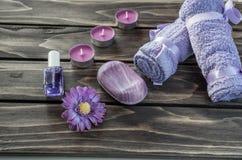 温泉概念 花、蜡烛、肥皂和浴紫色毛巾 免版税库存图片