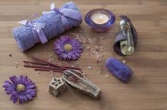 温泉概念 花、蜡烛、芳香盐、肥皂和紫色拖曳 库存照片