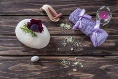 温泉概念 花、蜡烛、芳香盐和浴紫色towe 免版税库存照片