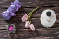 温泉概念 花,蜡烛nd浴紫色毛巾 免版税图库摄影