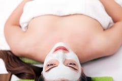 温泉概念 递应用在女性面孔的养育的面具在温泉沙龙 免版税图库摄影