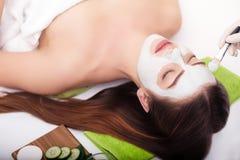 温泉概念 递应用在女性面孔的养育的面具在温泉沙龙 库存照片