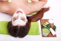 温泉概念 递应用在女性面孔的养育的面具在温泉 免版税库存照片