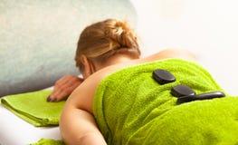 温泉沙龙。放松的妇女有热的石按摩。Bodycare。 免版税图库摄影