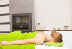 温泉沙龙。放松的妇女有热的石按摩。Bodycare。 库存照片