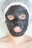 温泉沙龙的创造性的妇女与黑泥面罩 免版税库存照片
