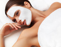 温泉沙龙的少妇与在面孔的化妆面具。 免版税库存图片