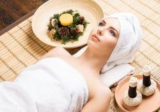 温泉沙龙的美丽,年轻和健康妇女在竹席子 S 库存照片