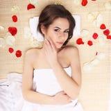 温泉沙龙的美丽,年轻和健康妇女在有红色白色玫瑰花瓣的竹席子 温泉、健康和医治用的概念 免版税图库摄影