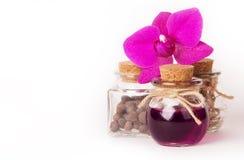 温泉的芳香油在花桃红色兰花围拢的一个玻璃小瓶 免版税库存图片
