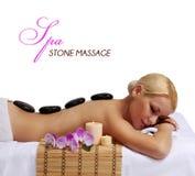 温泉石按摩。得到热的石头按摩的美丽的金发碧眼的女人 库存照片