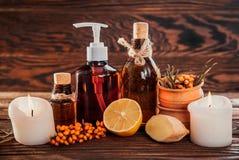 温泉精华包括海鼠李、柠檬和姜油和蜡烛 有机化妆用品概念 免版税库存图片