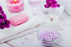 温泉精华包括蜡烛、盐、肥皂、油和兰花与毛巾 机体关心概念查出的白人妇女 库存图片