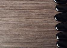 温泉背景。 在木的黑色石头 免版税库存照片