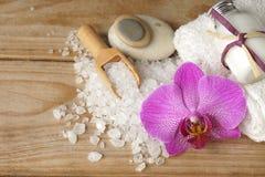 温泉设置了与白色毛巾、海盐、木小铲和一朵明亮的兰花花,您的文本的拷贝空间在左边 库存照片