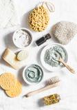 温泉辅助部件-坚果洗刷,擦,面部刷子,自然肥皂,黏土面罩,浮岩,在轻的背景的精油 免版税库存照片