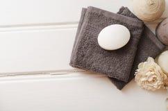温泉静物画-一块肥皂和毛巾在木背景 免版税库存照片