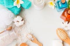 温泉题材框架在白色木背景反对 腌制槽用食盐、梳子、化妆水和毛巾与拷贝空间 图库摄影
