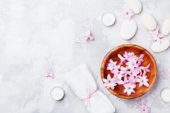 温泉,芳香疗法,与按摩小卵石的秀丽背景,充满了香气花从上面浇灌和在石桌上的蜡烛 免版税库存图片