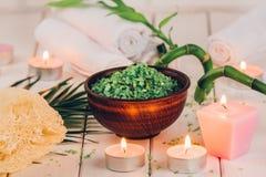 温泉 在陶瓷碗、温泉毛巾、桃红色有气味的蜡烛和竹子的绿色草本spirulina盐 定调子,表面无光泽 免版税库存图片