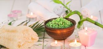 温泉 在陶瓷碗、温泉毛巾、桃红色有气味的蜡烛和竹子的绿色草本spirulina盐 库存图片