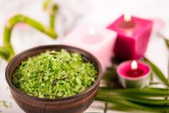 温泉 在陶瓷碗、温泉毛巾、桃红色有气味的蜡烛和竹子的绿色草本spirulina盐 免版税库存照片