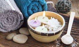 温泉 在水、棉花毛巾和腌制槽用食盐的灼烧的蜡烛 免版税图库摄影