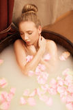温泉 女孩洗与海盐和玫瑰花瓣的浴 免版税库存图片