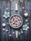 温泉治疗设置了与身体关心化妆用品、碗有花的在水中和蓝色海盐在土气木背景 免版税图库摄影